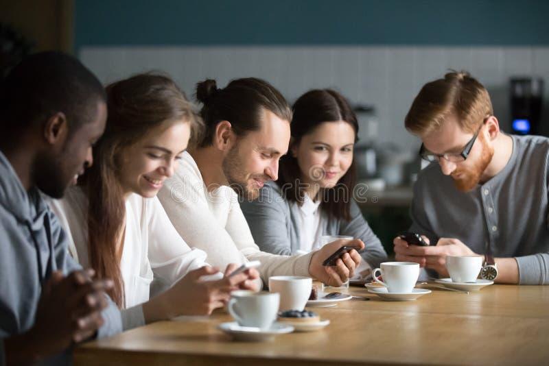 Amigos multi-étnicos que encontram-se no café usando dispositivos imagens de stock royalty free