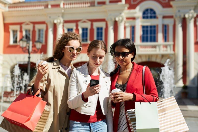 amigos Multi-?tnicos que usan el app que hace compras fotografía de archivo