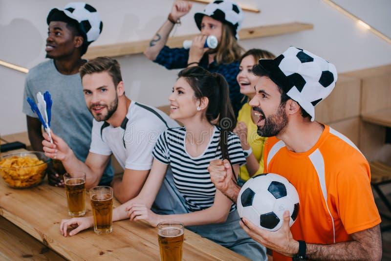 amigos multiculturais em chapéus da bola de futebol que comemoram gesticular pelas mãos e que olham o fósforo de futebol imagens de stock royalty free