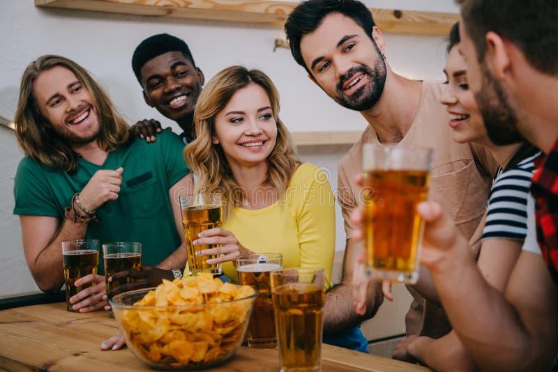 amigos multiculturais felizes com cerveja e microplaquetas que olham o fósforo e a fala de futebol fotos de stock