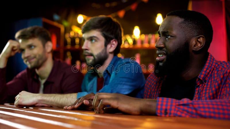 Amigos multirraciais emocionais infelizes, fósforo perdedor da equipe nacional, tempo no bar imagem de stock