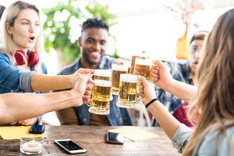 Amigos multirraciais felizes que bebem e que brindam a cerveja na barra da cervejaria - conceito da amizade com os jovens que têm imagens de stock royalty free