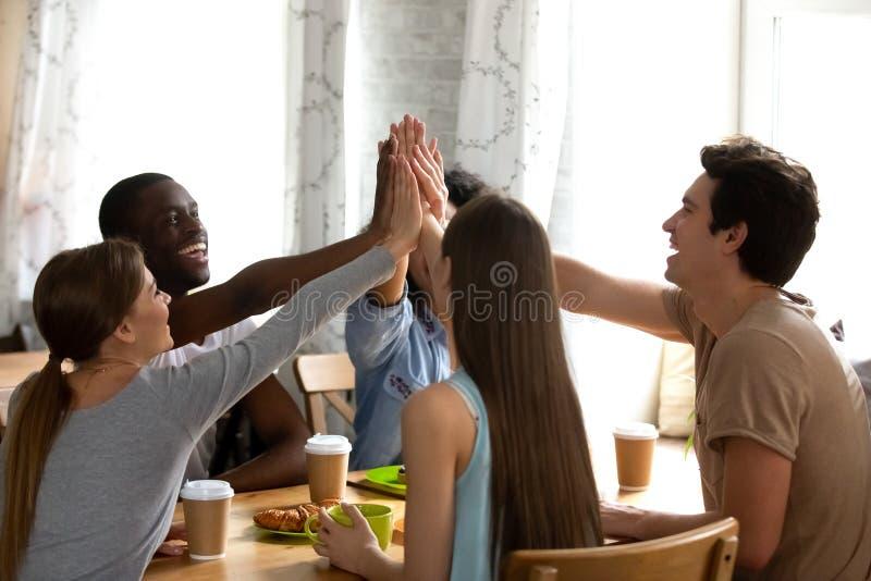Amigos multirraciais felizes que dão altamente cinco, cumprimentando no encontro no café foto de stock royalty free
