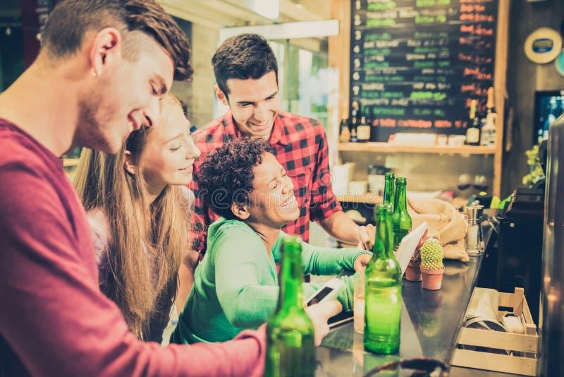 Amigos multirraciais que bebem a cerveja e que têm o divertimento na barra do cocktail imagem de stock