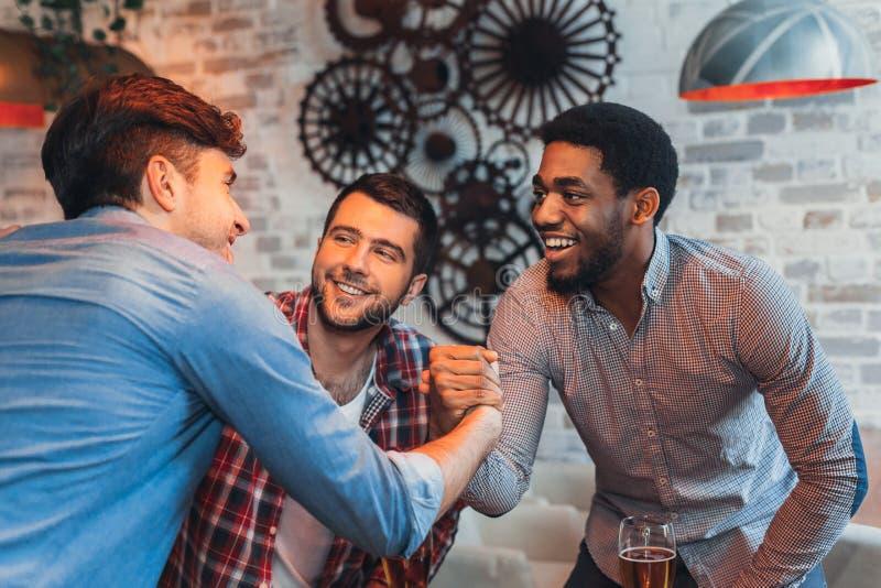 Amigos multirraciais que cumprimentam-se no bar da cerveja imagens de stock royalty free