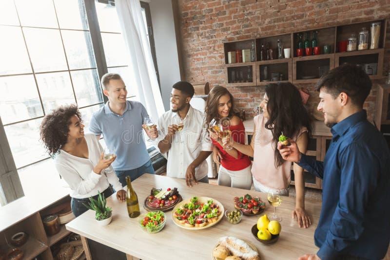 Amigos multirraciais que falam e que apreciam o partido em casa fotografia de stock royalty free