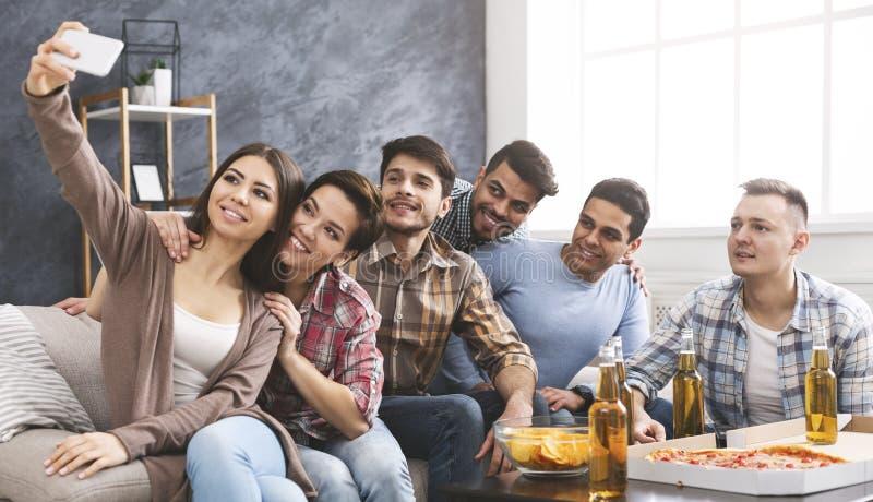 Amigos multirraciais que fazem o selfie junto que tem o partido da casa fotos de stock royalty free