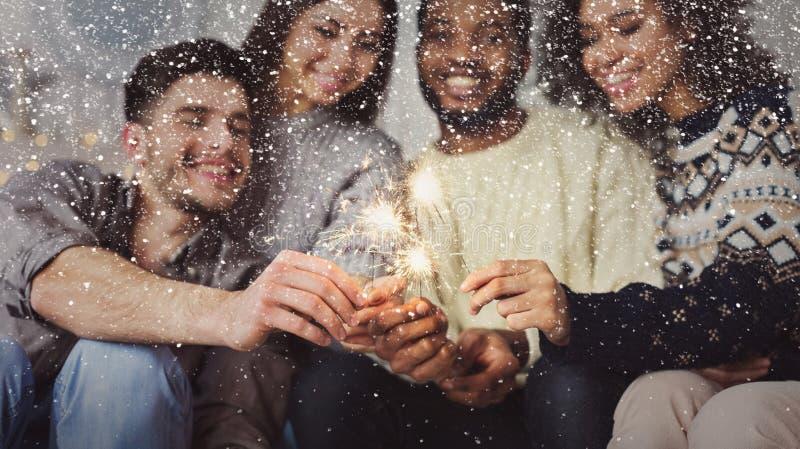 Amigos multirraciais que guardam luzes de bengal imagens de stock royalty free
