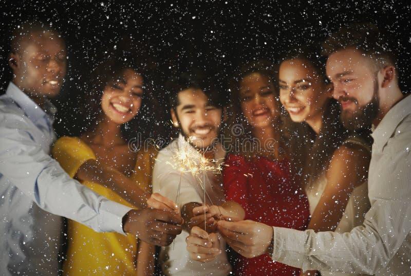 Amigos multirraciais que guardam luzes de bengal no partido fotografia de stock