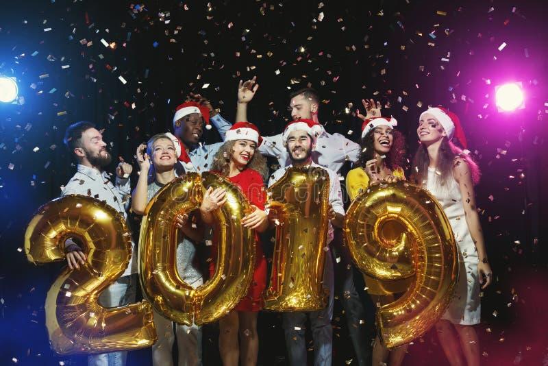 Amigos multirraciais que guardam um símbolo de 2019 anos no partido do ano novo imagens de stock