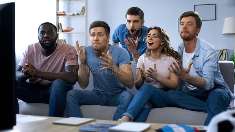 Amigos multirraciais que olham o jogo dos esportes junto, decepcionado com resultado imagens de stock royalty free