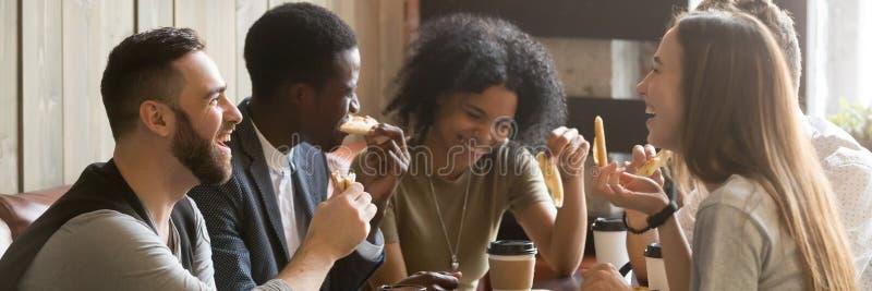 Amigos multirraciales de la imagen horizontal que beben el café que come la pizza en el café imagen de archivo libre de regalías