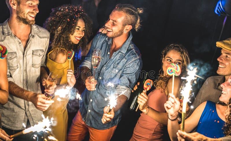Amigos multirraciales que beben la diversión en la celebración del festival del verano - gente joven que bebe y que baila en desp imagen de archivo libre de regalías