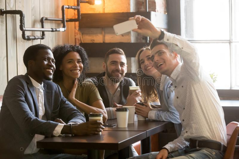 Amigos multirraciales que sonríen haciendo el selfie en café imagen de archivo libre de regalías