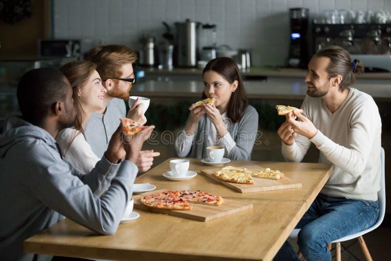 Amigos multirraciales sonrientes que hablan el café de consumición que come la pizza imagen de archivo