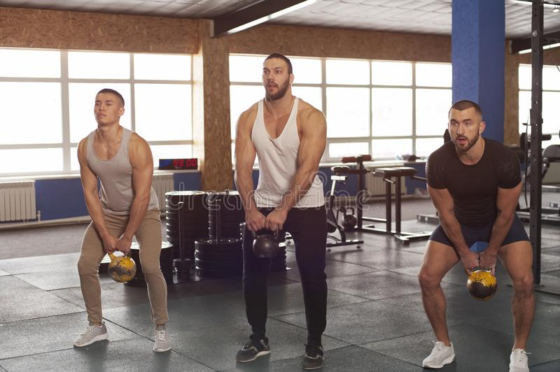 Amigos musculares masculinos aptos que se resuelven en gimnasio foto de archivo libre de regalías