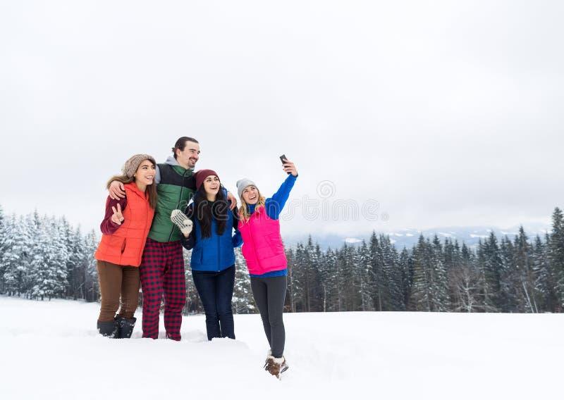 Amigos na floresta de tomada superior da neve do inverno da foto de Selfie da montanha, grupo de sorriso feliz dos jovens imagens de stock