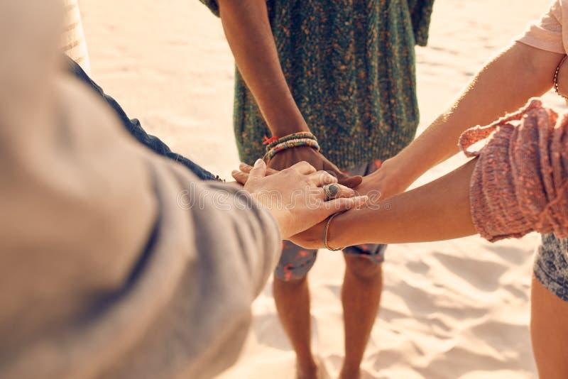 Amigos na praia que une as mãos imagem de stock