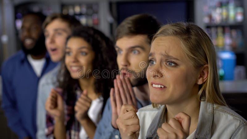 Amigos nervosos que olham o campeonato em linha, esperando para a vitória na competição imagem de stock