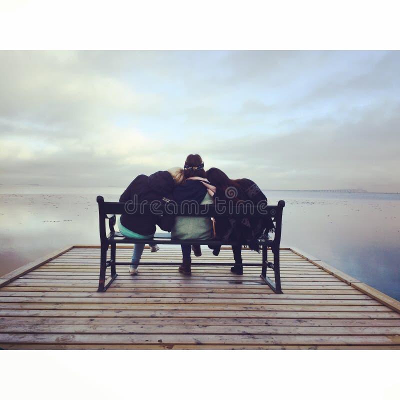 Amigos no banco no lago