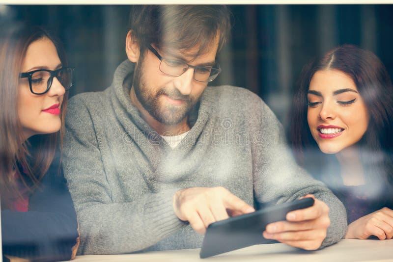 Amigos no café usando a tecnologia fotos de stock royalty free