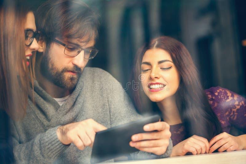 Amigos no café usando a tecnologia fotografia de stock royalty free