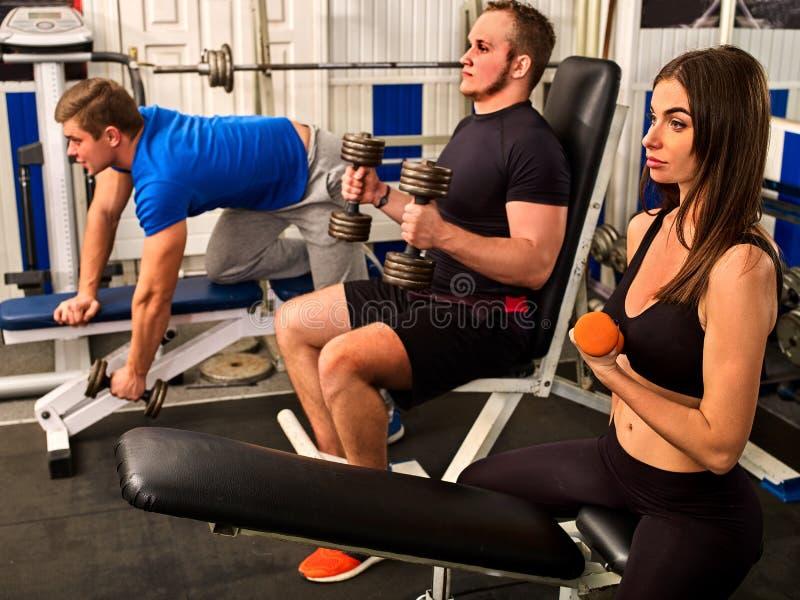 Amigos no exercício do gym com equipamento da aptidão Mulheres do treinamento imagem de stock