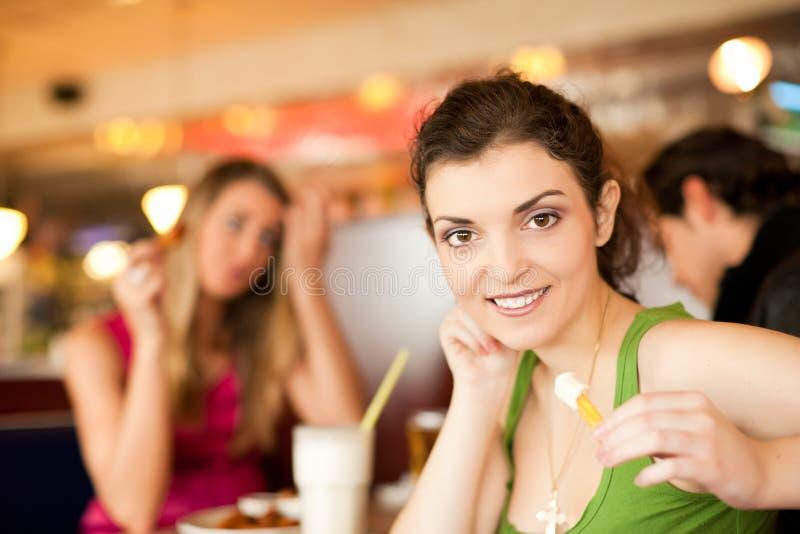Amigos no restaurante que comem o fast food fotografia de stock royalty free