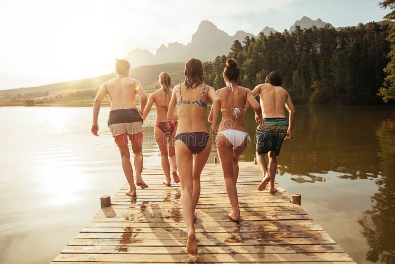 Amigos novos aproximadamente a saltar no lago de um cais fotografia de stock