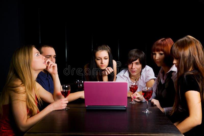 Amigos novos com portátil em uma barra. imagens de stock
