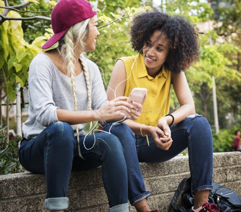 Amigos novos da fêmea adulta que escutam a música com seu smar imagens de stock