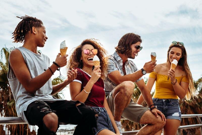 Amigos novos de sorriso que comem o gelado fora fotografia de stock