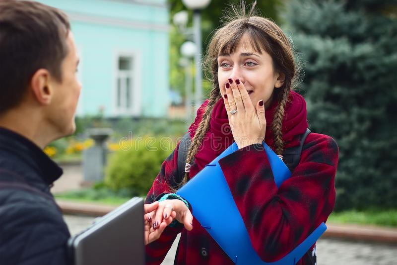 Amigos novos do estudante que falam na faculdade Tentativa da menina para mostrar como seu marido declarou no amor fotos de stock