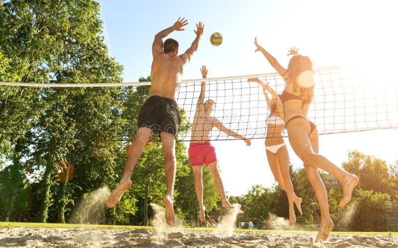 Amigos novos do grupo que jogam o voleibol na praia fotos de stock