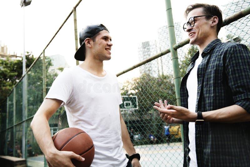 Amigos novos do homem adulto que jogam o basquetebol no parque foto de stock royalty free