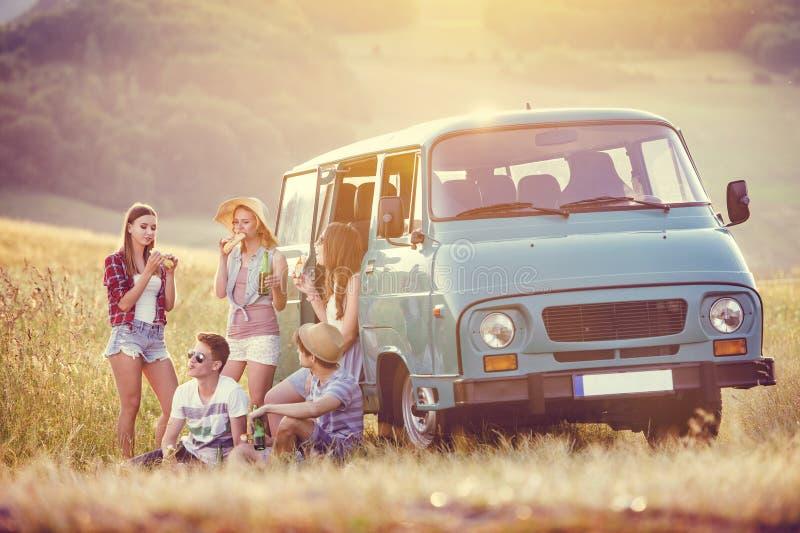 Amigos novos do moderno na viagem por estrada imagens de stock