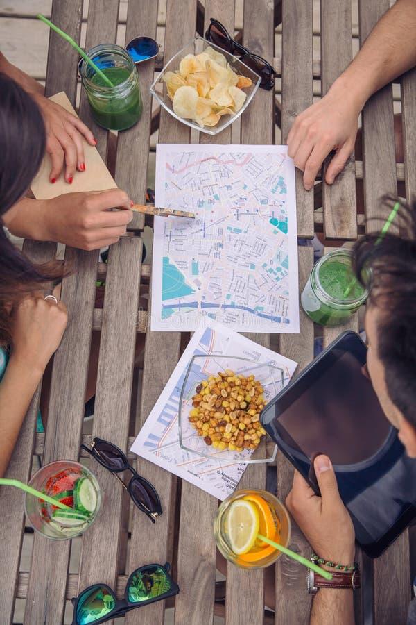 Amigos novos do turista que olham mapas dentro sobre uma tabela imagem de stock