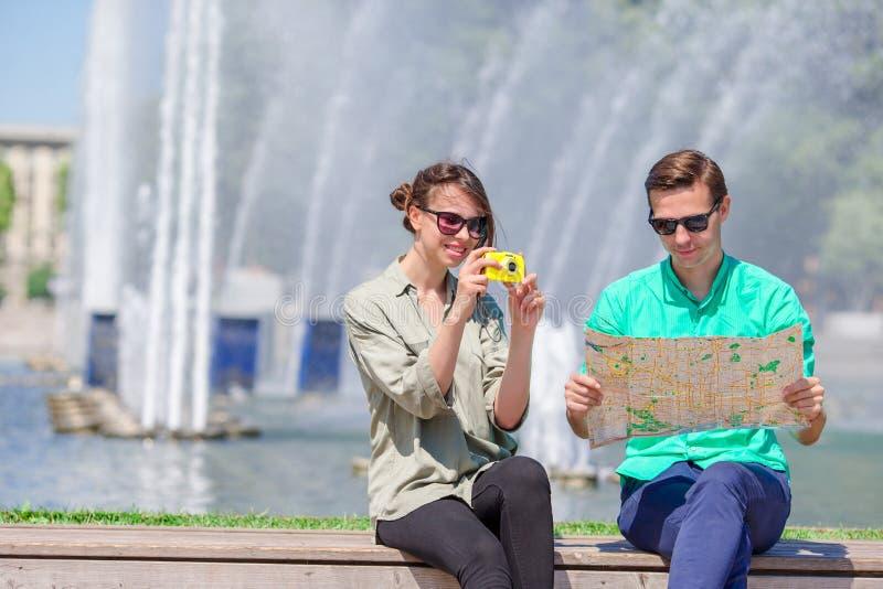 Amigos novos do turista que viajam em feriados no sorriso de Europa feliz Menina que toma fotos no parque e no homem com cidade fotografia de stock