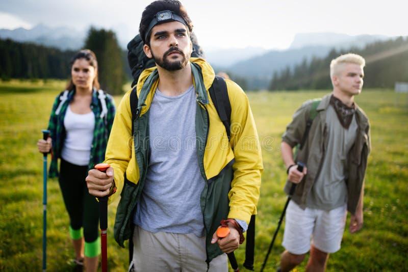 Amigos novos em uma caminhada do país Grupo de pessoas que caminha através do campo foto de stock