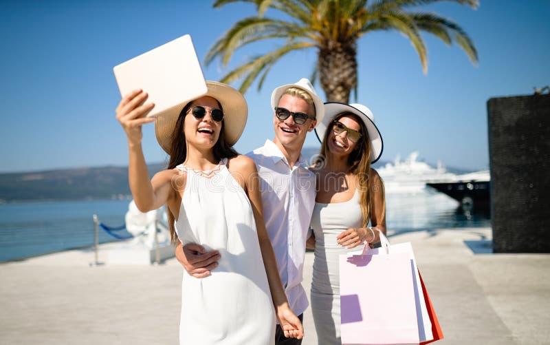 Amigos novos felizes em férias luxuosas Curso, compra, divertimento, conceito dos amigos imagens de stock