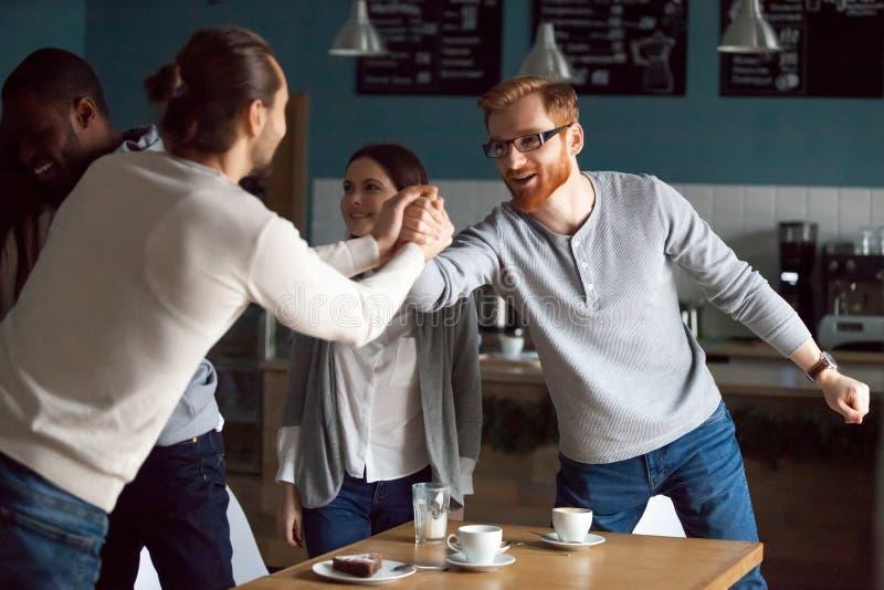Amigos novos felizes que cumprimentam na reunião amigável no café foto de stock