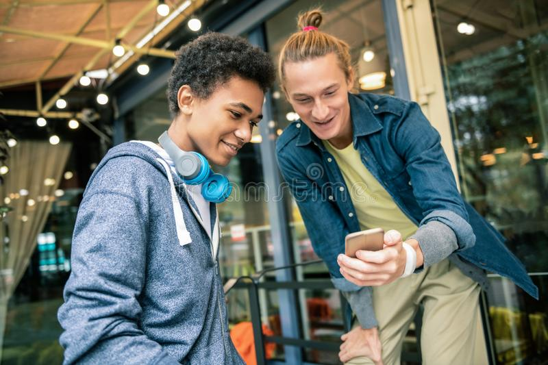 Amigos novos felizes que usam o dispositivo tecnologico novo imagem de stock