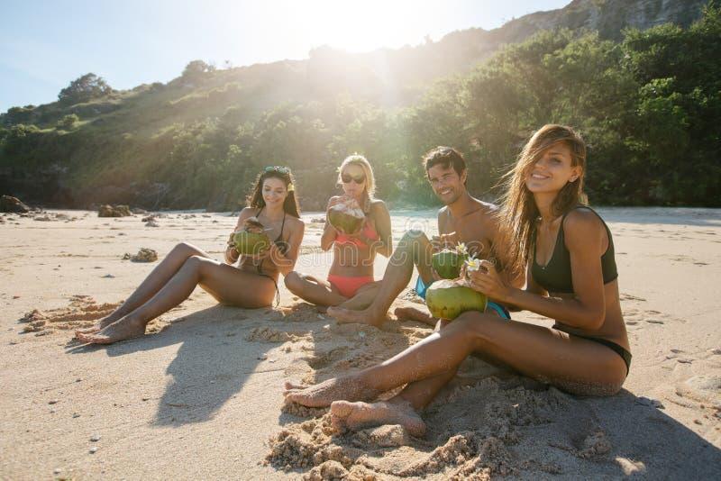 Amigos novos que apreciam férias de verão na praia foto de stock royalty free