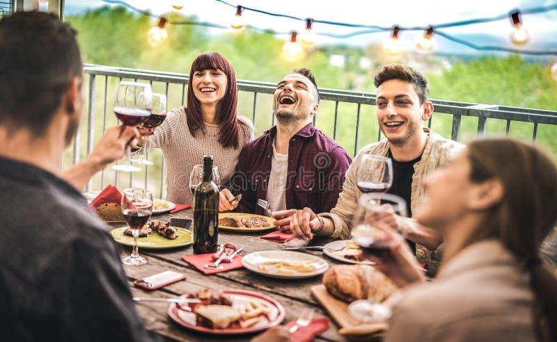 Amigos novos que comem o vinho tinto bebendo do divertimento no partido de jantar da sótão de luxo do balcão - pessoa feliz que c fotografia de stock
