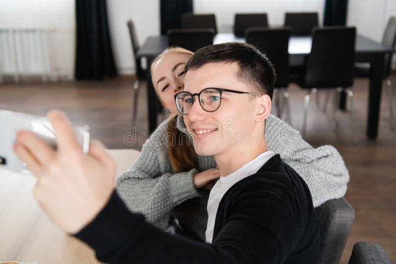 Amigos novos que fotografam-se com telefone celular em um café foto de stock