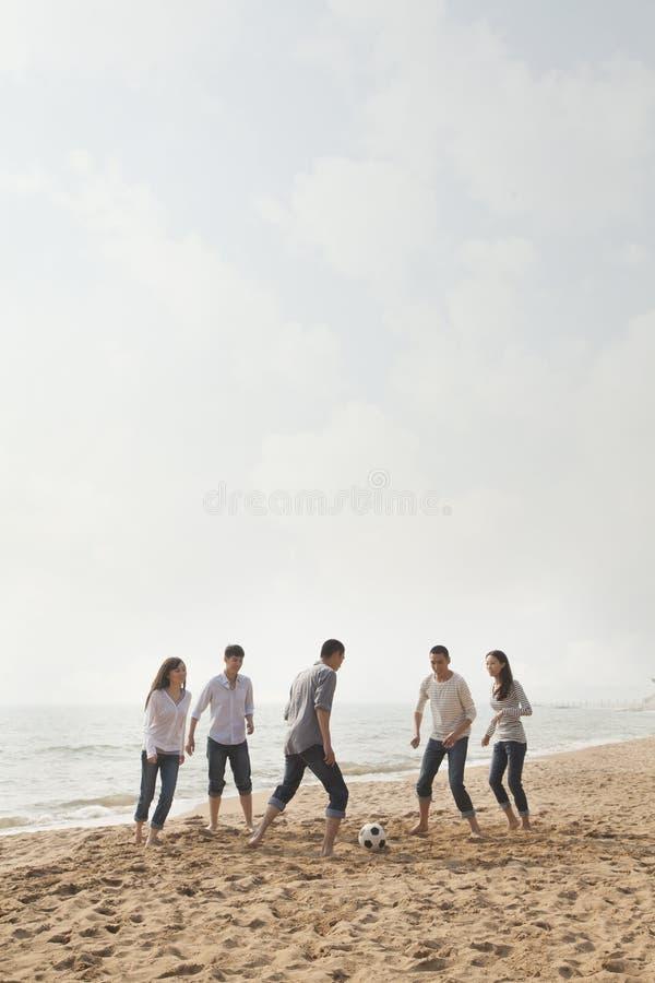Amigos novos que jogam o futebol e que têm o divertimento na praia imagens de stock