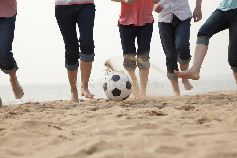 Amigos novos que jogam o futebol na praia foto de stock