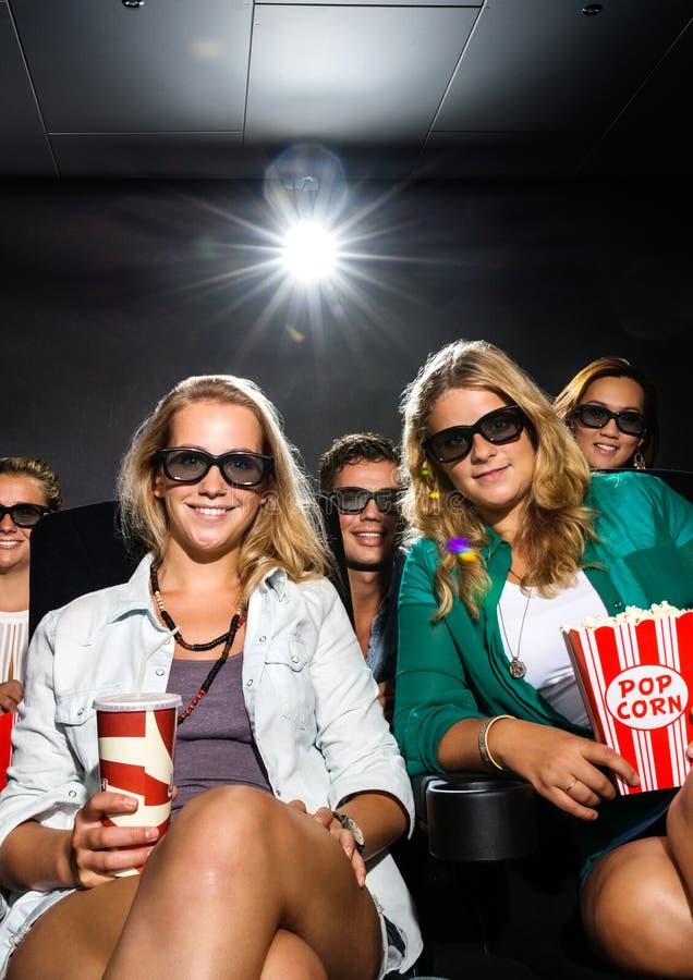 Amigos novos que olham o filme 3D no teatro imagem de stock