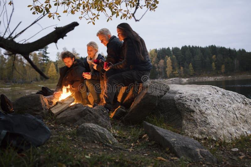 Amigos novos que relaxam pela fogueira sobre Lakeshore imagens de stock royalty free