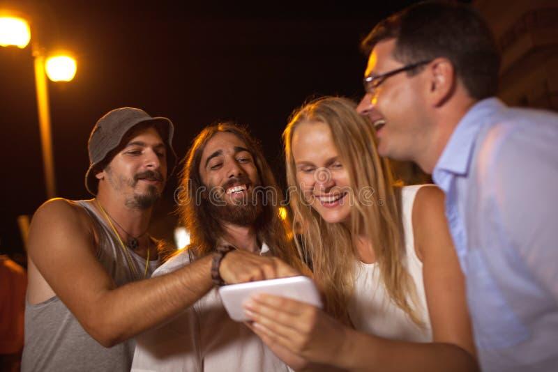 Amigos novos que riem do que vê no móbil imagens de stock royalty free